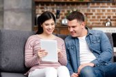 smiling young pregnant couple using digital tablet together at home