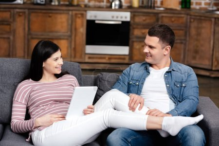 happy young man looking at smiling pregnant wife using digital tablet at home