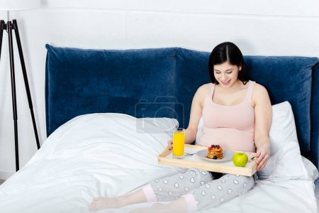 smiling young pregnant woman holding tray with breakfast in bed