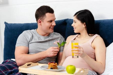 happy young pregnant couple eating breakfast in bed, man presenting flower to woman
