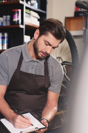 focused young worker in apron taking notes on clipboard at bicycle shop