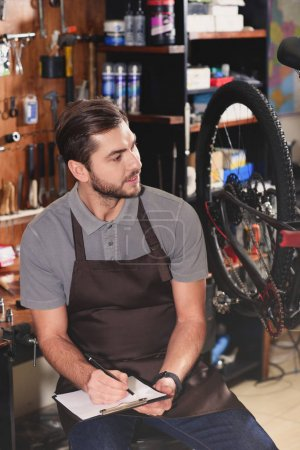 handsome young bicycle mechanic sitting and taking notes in workshop
