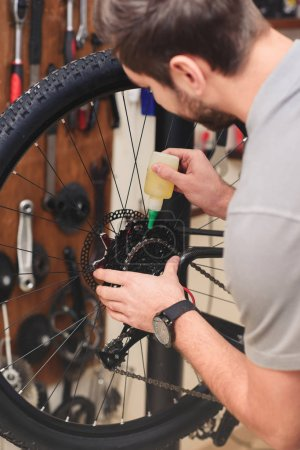 cropped shot of young repairman oiling bicycle chain in workshop