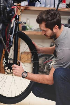 Photo for Young male worker in apron fixing bicycle in workshop - Royalty Free Image