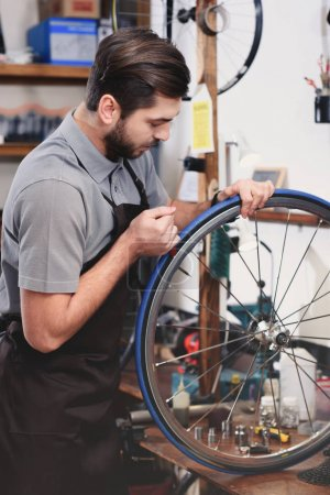 young mechanic in apron repairing bicycle wheel in workshop