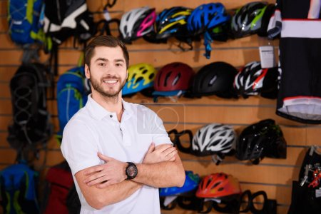 handsome young seller standing with crossed arms and smiling at camera in bicycle shop