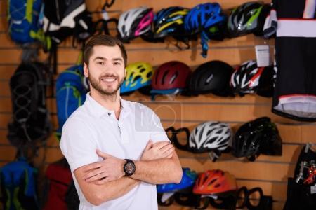 Photo pour Beau jeune vendeur debout avec les bras croisés et souriant à la caméra dans le magasin de vélo - image libre de droit