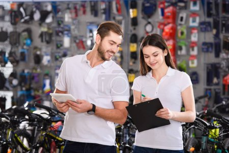 smiling young managers working with clipboard and digital tablet in bicycle shop