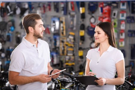 smiling young workers with clipboard and digital tablet looking at each other in bike shop