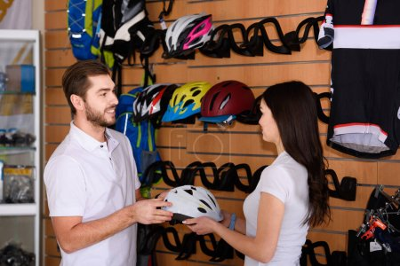 side view of young managers holding bicycle helmet and looking at each other while working together in bike shop