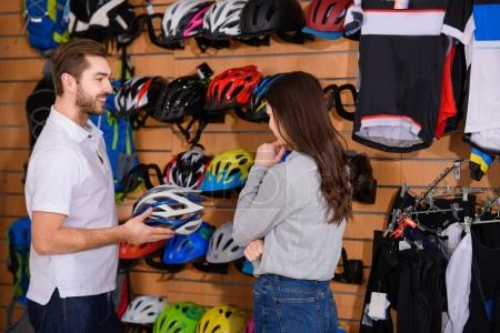 smiling male manager showing bicycle helmet to young woman in bike shop