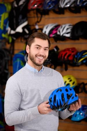 handsome young man holding bicycle helmet and smiling at camera in workshop