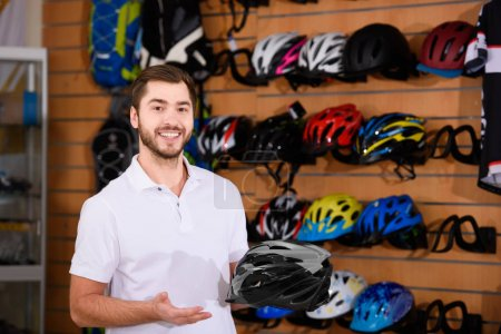 young male worker holding bicycle helmet and smiling at camera in bike shop