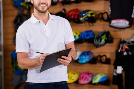 cropped shot of smiling young manager writing on clipboard in bike shop