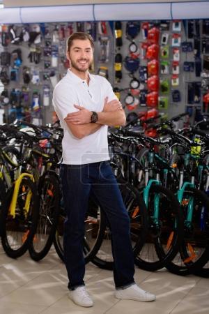 Photo pour Beau jeune homme debout avec les bras croisés et sourire à la caméra dans le magasin de vélos - image libre de droit