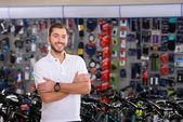 confident handsome young manager standing with crossed arms and smiling at camera in bicycle shop