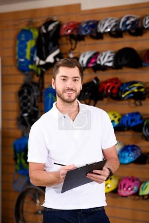 handsome young man writing on clipboard and smiling at camera in bicycle shop