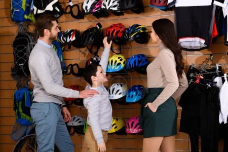 smiling young parents looking at son choosing bicycle helmet in bike shop