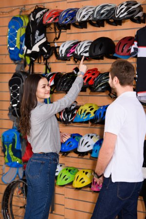 smiling young woman pointing with finger at bicycle helmet and looking at seller in bike shop