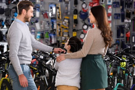 back view of young parents with son choosing bicycles in bike shop