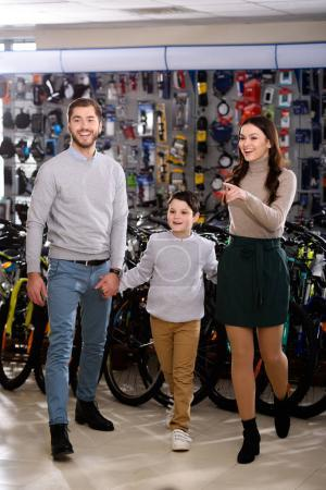 happy parents with little son shopping together in bicycle shop