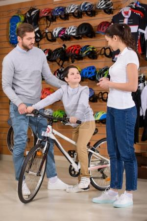 cute happy boy sitting on new bicycle while father and seller standing nearby in bike shop