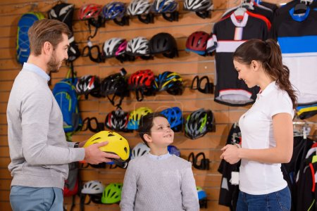 smiling young woman looking at father and son choosing bicycle helmet in bike shop