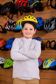 cute little boy wearing bicycle helmet and smiling at camera in bike shop