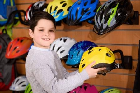 cute little boy holding bicycle helmet and smiling at camera in bike shop