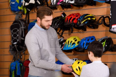 father and cute little son holding bicycle helmet in bike shop