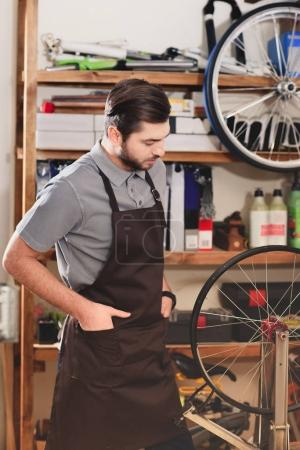 confident young worker in apron looking at bicycle wheel in workshop