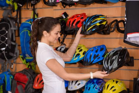smiling young woman holding bicycle helmets in bike shop