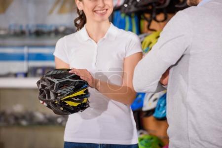 cropped shot of smiling seller showing bicycle helmet to customer in bike shop