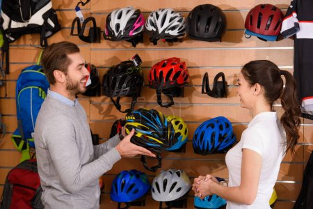 side view of seller and customer looking at each other while choosing bicycle helmet in bike shop