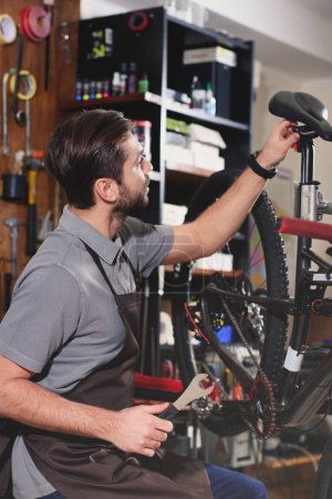 young repairman in apron fixing bicycle in workshop