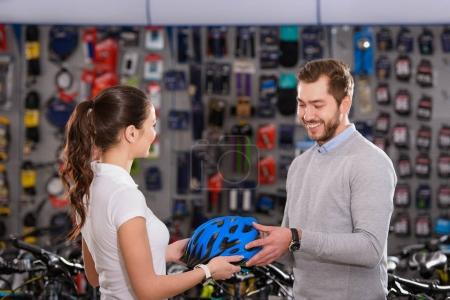 young female seller showing helmet to smiling customer in bike shop