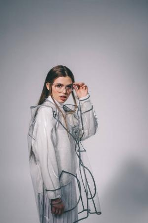 portrait of fashionable woman in trendy raincoat and eyeglasses looking at camera on grey background