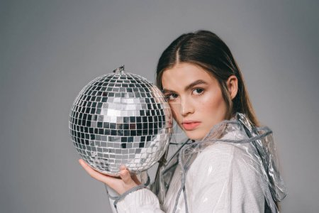 portrait of fashionable woman with disco ball in hands looking at camera isolated on grey