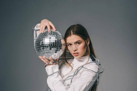portrait of young fashionable woman with disco ball in hands isolated on grey