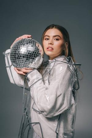 portrait of young woman in fashionable raincoat with disco ball isolated on grey