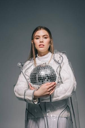 portrait of stylish young woman with disco ball in hands isolated on grey