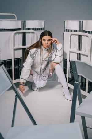 Photo pour Femme à la mode en vêtements blancs posant avec des chaises pliables derrière sur fond gris - image libre de droit