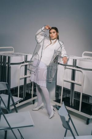 stylish woman in white clothing and raincoat posing with collapsible chairs behind on grey background