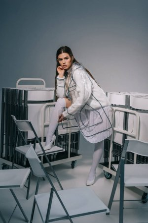 fashionable woman in white clothing and raincoat posing with collapsible chairs behind on grey background