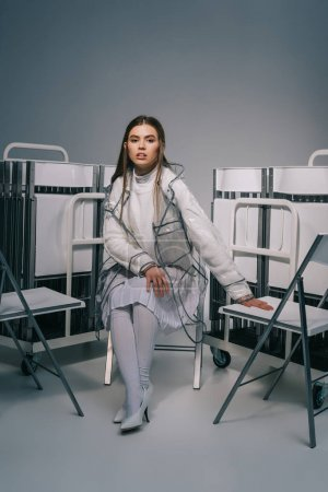 fashionable woman in white clothing posing with collapsible chairs behind on grey background