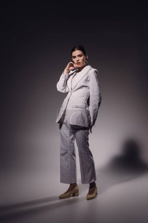 young fashionable woman in white suit posing on dark backdrop