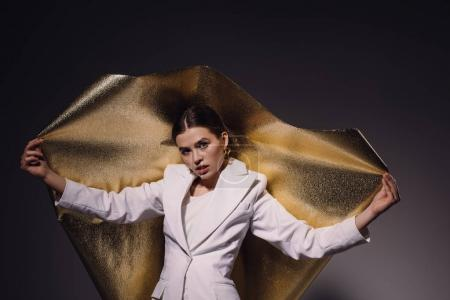 portrait of woman in stylish suit with golden wrapping paper in hands looking at camera on dark background