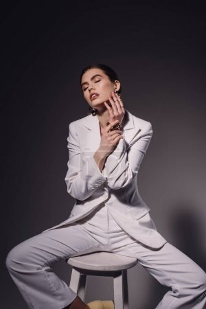 portrait of fashionable woman in white suit sitting on chair on dark background