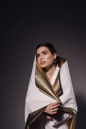 portrait of fashionable pensive woman in white and golden wrapping paper looking away on dark backdrop