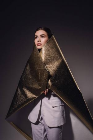 portrait of fashionable pensive woman in golden wrapping paper looking away on dark backdrop